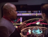 Benjamin Sisko and Jadzia Dax stand in front of a large wall monitor which shows a schematic of the strategy for attacking Deep Space Nine.