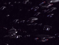 Dozens of Starfleet ships of many types fly in formation with Starbase 375 in the background.