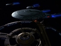A Galaxy-class starship docks at Deep Space 9, while two other Starfleet ships patrol in the background.
