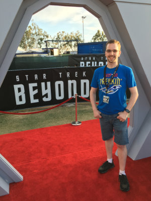Dan standing in a futuristic-looking open doorway on the red carpet at the premiere of Star Trek Beyond, with a black banner showcasing the movie title in the background.